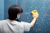 stock photo of soapy  - woman in a gray shirt washes blue tile with a cloth with soapy foam in the bathroom - JPG