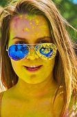 stock photo of holi  - happy girl in sunglasses at Holi Festival  - JPG