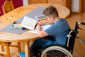 picture of wheelchair  - disabled boy in wheelchair doing homework in the living room - JPG