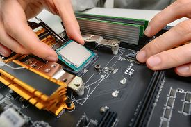 stock photo of cpu  - Hands of a technician assembling computer hardware parts as a new cpu is being mounted unto the motherboard studio closeup - JPG