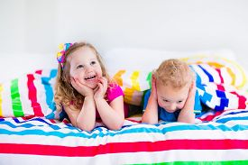 stock photo of boys night out  - Two kids sleeping in bed under colorful blanket - JPG