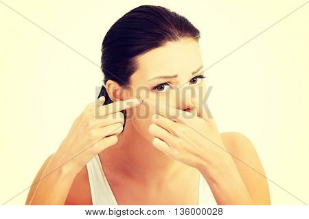 Young woman with pimple on her face. Trying to squeeze it.