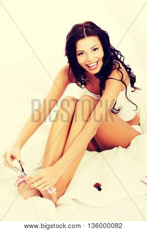 Attractive woman cutting her nails.