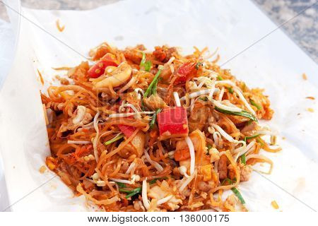 Fried noodle Thai style with prawns. Stir fry noodles with seafood (Pad Thai) Thai Cuisine on white color wrapper food.