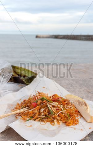 Fried noodle Thai style with prawns. Stir fry noodles with seafood (Pad Thai) Thai Cuisine on white color wrapper food. Sea background