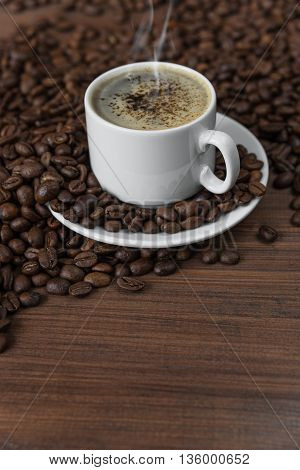 White porcelain cup of coffee on the wooden background with coffee beans; whith spase for text