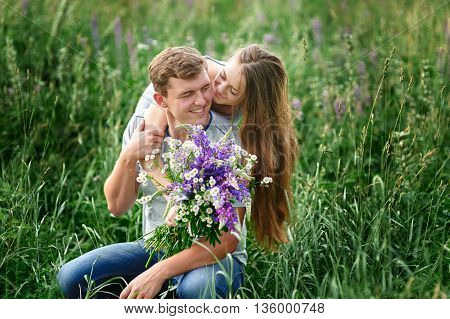 beautiful woman with a bouquet of wild flowers hugging man sitting on the grass in a meadow.