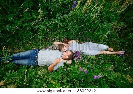 Young happy beautiful couple man and woman lying outdoors on green grass.