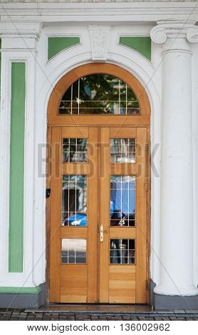 Ornate stained wood doors with wrought iron grating over glass windows.
