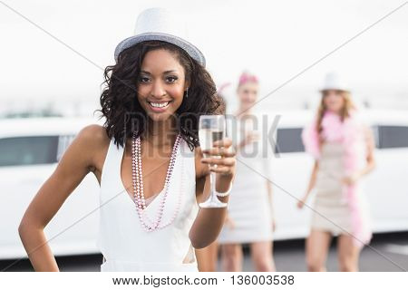 Happy friends drinking champagne in front of a limousine on a night out