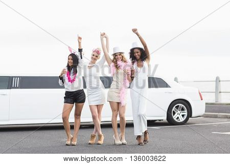 Happy friends dancing in front of a limousine on a night out