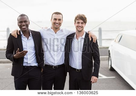 Handsome men posing next to a limousine on a night out