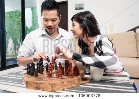 Indonesian couple playing chess at home