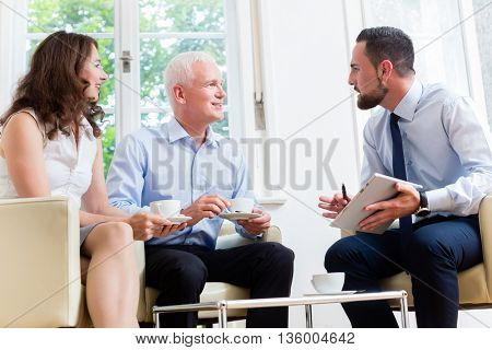 Financial advisor consulting couple in retirement planning in modern, luminous office