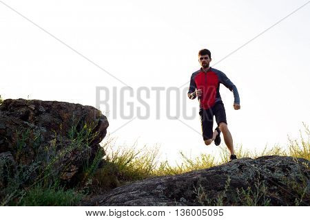 Young Sportsman Running on the Rocky Mountain Trail in the Evening. Active Lifestyle Concept