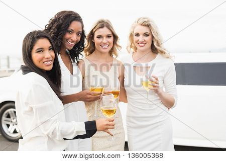 Well dressed men drinking wine next to a limousine on a night out