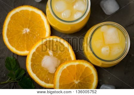 Orange juice in glass with mint fresh fruits. selective focus top view