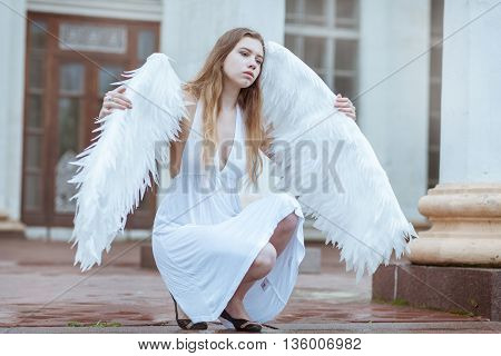 Girl angel with big white wings sitting and looking away