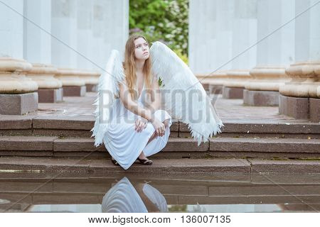 Girl with white wings sitting near the water among the columns