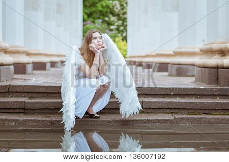 Girl angel pondered. She sits near the water and looking at the sky