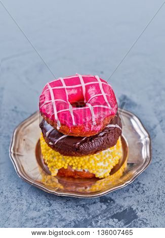 Glazed Doughnuts with colourful sprinkles and icing on a vintage metal plate over granite background