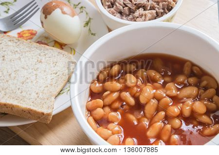 Baked beans in tomato sauce on bowl with bread and tuna steak