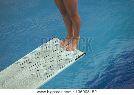 Lady diver preparing to dive from the springboard into a swimming pool