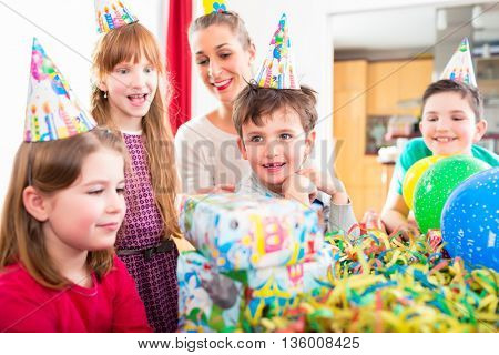Child unwrapping birthday gift with friends at home birthday party, mom is helping