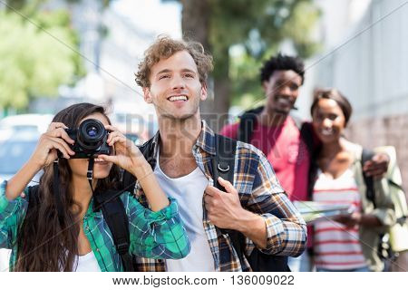 Woman standing with man taking photo with couple standing behind them