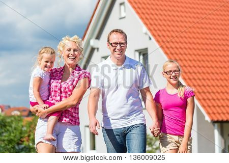 Family of Parents and children standing proud in front of home