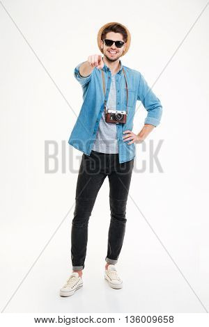 Smiling young male photographer with old vintage camera standing and pointing on you over white background