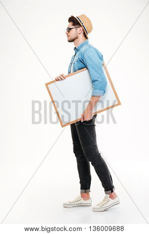 Full length of serious young man walking and holding blank whiteboard over white background