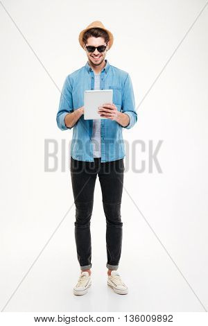 Cheeful young man in hat and sunglasses standing and using tablet over white background
