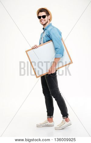 Happy smiling young man walking and holding blank whiteboard over white background