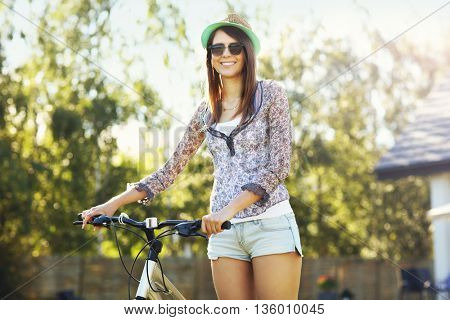 Picture of a happy woman with bike in the garden