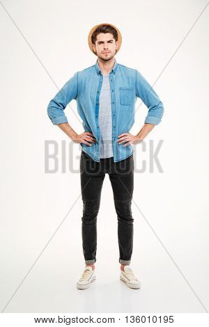 Serious strict young man standing with hands on waist over white background
