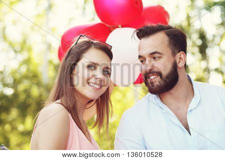 A picture of romantic couple standing outside with baloons