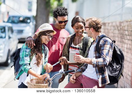 Man sitting on bicycle showing mobile phone to his friends