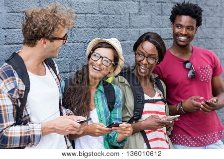 Group of friends using mobile phone and having fun