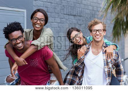Portrait of happy young men giving piggyback to women