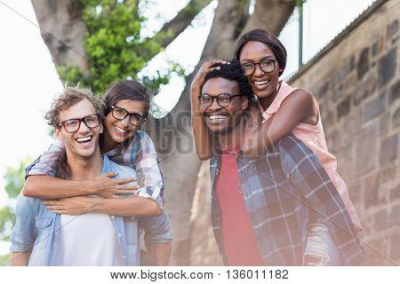 Portrait of young men giving piggyback to women
