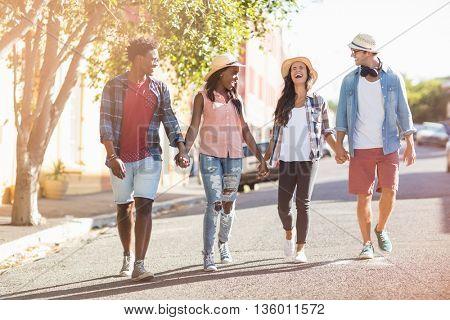 Happy friends walking hand in hand