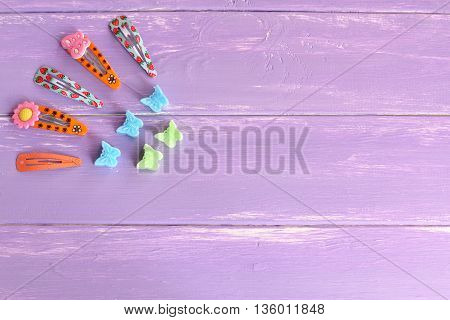 Bright colored hair clips for girls on lilac wooden background with copy space for text. Set of colorful hair clips. Girl fashion background