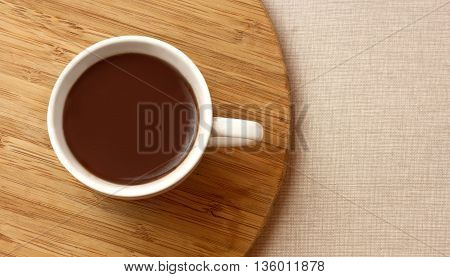 A photo of a cup of dark hot chocolate shot from above on a wooden board on a textile texture with copyspace