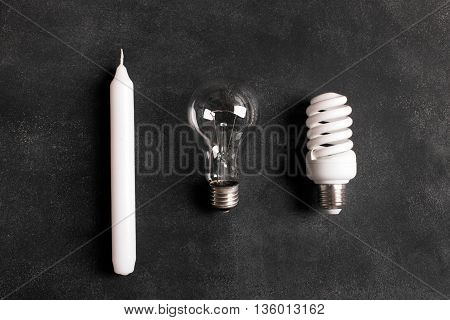 White candle and electric bulbs on the black chalkboard. Concept describing the evolution of lighting