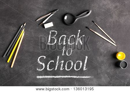 Back to school concept. Compass magnifying glass brush eraser on the black chalkboard