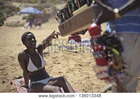 Woman pointing at imitation products at the beach