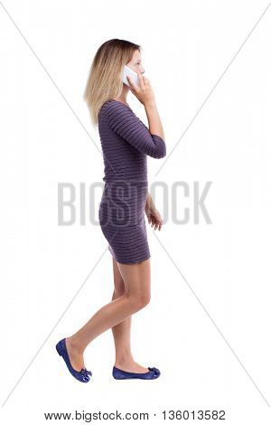side view of a woman walking with a mobile phone. back view ofgirl in motion.  backside view of person.  Rear view people collection. Girl in a short dress is left talking to the white smartphone.