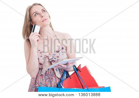 Pensive Attractive Female With Debit Card, Tablet And Shopping Bags