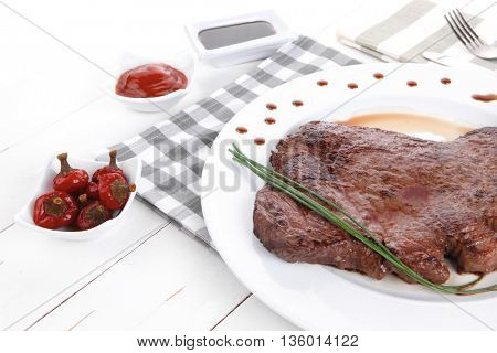 fresh rich juicy grilled beef meat steak fillet on white plate over wooden table decorated with sauces and cutlery new york style